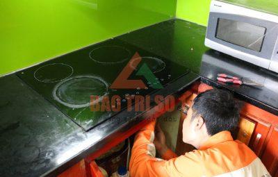 kỹ thuật đang trong quá trình sửa chữa bếp từ tại nhà cho khách hàng